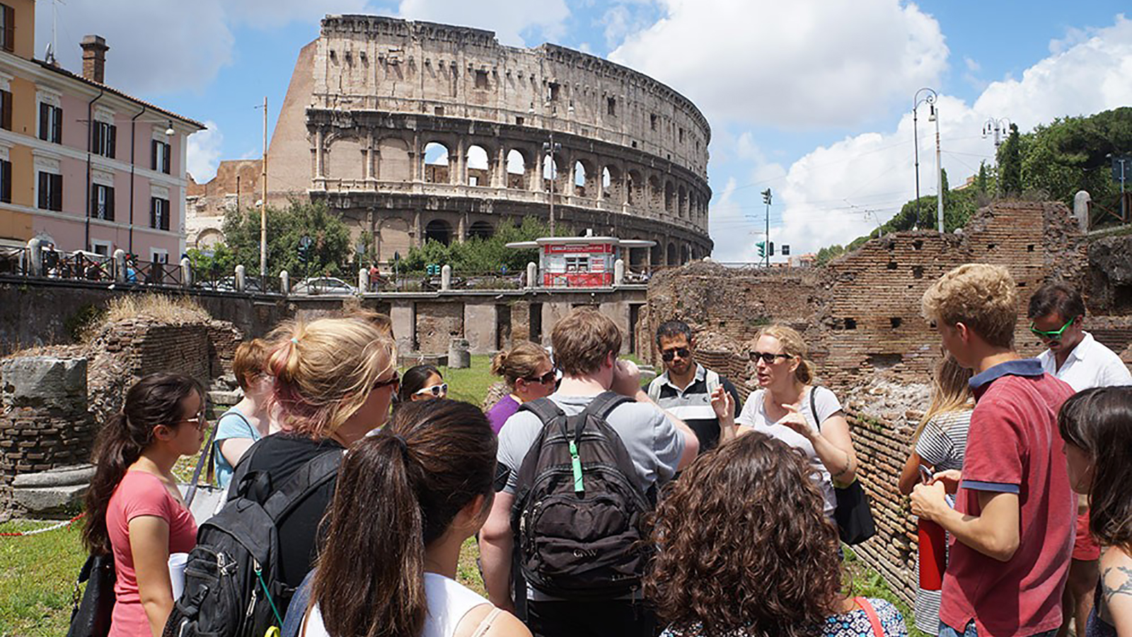 Participants in the Classical Summer School receive a lecture outside the Roman Colosseum